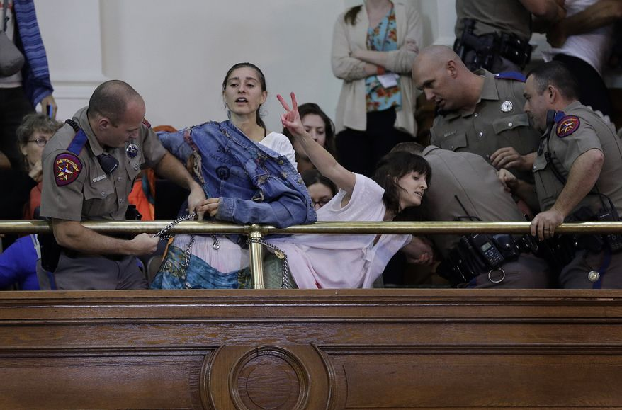 Texas state troopers remove pro-choice protesters from the Texas Senate gallery as the chamber debates abortion bill HB2 on Friday, July 12, 2013, in Austin, Texas. (AP Photo/Eric Gay)