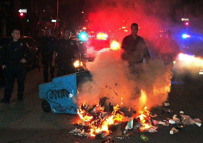 Oakland police officers work to extinguish a fire during a protest early on Sunday, July 14, 2013, in Oakland, Calif., after George Zimmerman was found not guilty in the 2012 shooting death of teenager Trayvon Martin. (AP Photo/Bay Area News Group, Anda Chu)