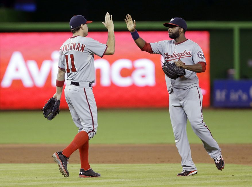Washington Nationals third baseman Ryan Zimmerman, left, celebrates with center fielder Denard Span, right, after the Nationals defeated the Miami Marlins 5-2 in 10 innings of a baseball game, Sunday, July 14, 2013 in Miami. Span had three hits, including a tie breaking two-out RBI double in the 10th inning. (AP Photo/Wilfredo Lee)