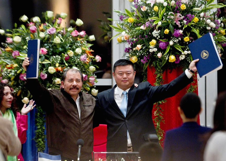 Nicaraguan President Daniel Ortega and Wang Jing display an agreement granting the Chinese businessman the exclusive right to develop a multibillion-dollar waterway to rival the Panama Canal. Construction is set to be completed by 2019, Mr. Wang said. (Associated Press)