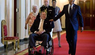 President Barack Obama with former President George H. W. Bush, first lady Michelle Obama and former first lady Barbara Bush, behind left, arrive to present the 5,000th Daily Point of Light Award to Floyd Hammer and Kathy Hamilton, a retired couple and farm owners from Union, Iowa, in the East Room of the White House in Washington, Monday, July 15, 2013. (AP Photo/Carolyn Kaster)