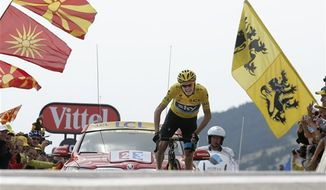 Stage winner and overall leader Christopher Froome of Britain crosses the finish line of the fifteenth stage of the Tour de France cycling race over 242.5 kilometers (150.7 miles) with start in in Givors and finish on the summit of Mont Ventoux pass, France, Sunday July 14, 2013. The riders will climb to an altitude of 1912 meters (6,273 Feet) as they tackle Mont Ventoux pass at the end of the longest stage of the 100th Tour de France edition. (AP Photo/Christophe Ena)