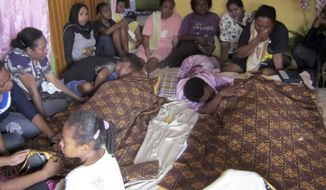 Relatives mourn around the bodies of Yanus Manibui and his wife, Anance Woyaa, in Nabire, Indonesia, on Monday, July 15, 2013. The two were among the victims in a stampede at the Kota Lama Sport Stadium after spectators rioted to protest a local boxer's loss. (AP Photo)