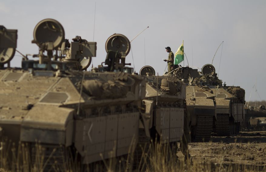 An Israeli soldier from the Golani Brigade reads a holy book as he stands atop an armored personnel carrier at a training ground in the Israeli-controlled Golan Heights near the border with Syria on Tuesday, June 25, 2013. (AP Photo/Ariel Schalit)
