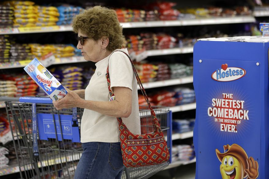 Shopper Jo Mullen picks up a box of Twinkies at a Wal-Mart store in Bristol, Pa., on Friday, July 12, 2013. The spongy yellow cakes, newly returned to store shelves, are a little smaller than the old Twinkies people remember eating. (AP Photo/Matt Rourke)