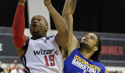 Washington Wizards Sundiata Gaines (19) goes up for a shot against Golden State Warriors Gary McGhee (52) in the first quarter of an NBA Summer League basketball game, Saturday, July 13, 2013, in Las Vegas. (AP Photo/Julie Jacobson)