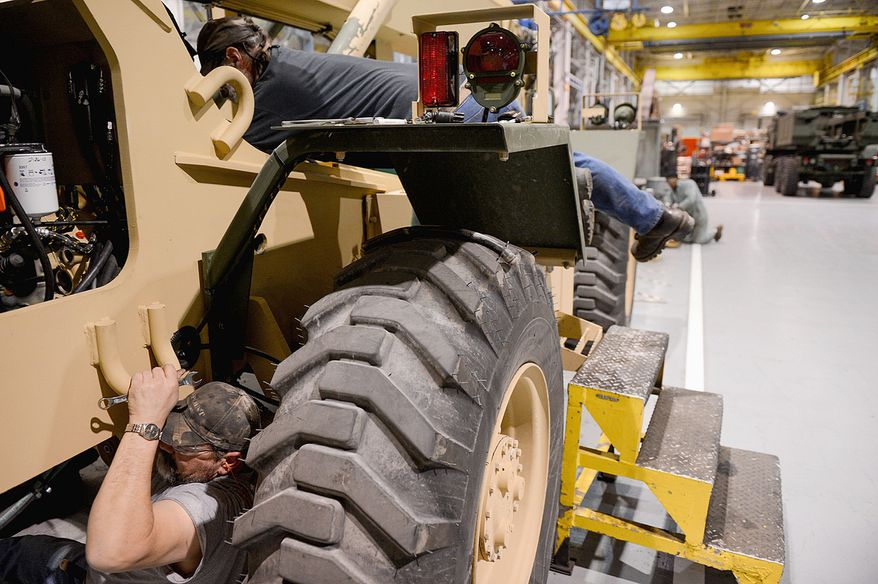Robert Dillman (bottom) of Blair Mills, Pa., works on a vehicle with Don Sites of Towngap, Pa. Mr. Dillman has been a government employee for 12 years, and Mr. Sites has worked at the Letterkenny Army Depot for four years, but their futures are uncertain. (Andrew Harnik/The Washington Times)