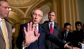 Senate Majority Leader Harry Reid, flanked by Sen. Jeff Merkley (right) and Sen. Tom Udall, hails a Democratic victory after averting a political meltdown, clearing the way for confirmation of presidential nominees. (Associated Press)