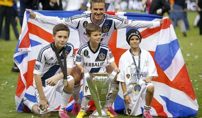 ** FILE ** Los Angeles Galaxy's David Beckham, top center, of England, poses with his sons, from left, Brooklyn, Romeo and Cruz after the Galaxy's 3-1 win in the MLS Cup championship soccer match against the Houston Dynamo in Carson, Calif., Saturday, Dec. 1, 2012. (AP Photo/Jae C. Hong)