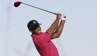 Tiger Woods of the US plays a shot off the 5th tee during a practice round for the British Open Golf Championship at Muirfield, Scotland, Tuesday July 16, 2013. (AP Photo/Alastair Grant)