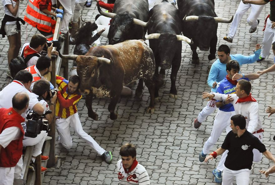 "CORRECTS DATE  - A runner is pushed by a ""Miura"" fighting bull during the eighth and last running of the bulls at the San Fermin festival, in Pamplona Spain on Sunday, July 14, 2013. Revelers from around the world arrive to Pamplona every year to take part in some of the eight days of the running of the bulls glorified by Ernest Hemingway's 1926 novel ""The Sun Also Rises."" (AP Photo/Alvaro Barrientos)"