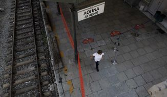 A cleaning worker walks in the empty central train station during a 24-hour strike in Athens, Tuesday, July 16, 2013. (AP Photo/Kostas Tsironis)