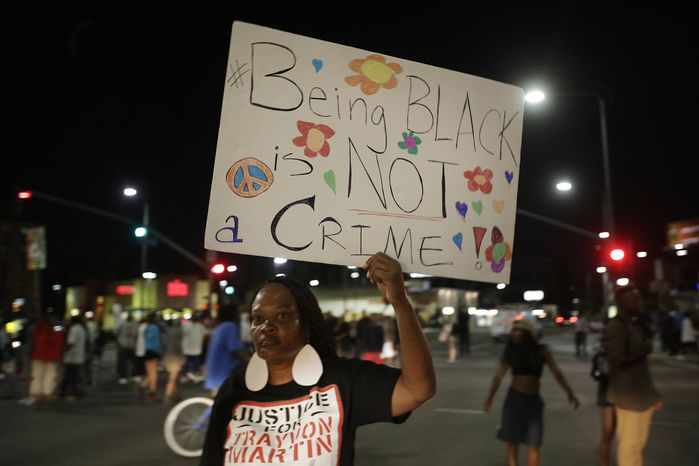 A woman holds up a sign during a demonstration in reaction to the acquittal of neighborhood watch volunteer George Zimmerman on Monday, July 15, 2013, in Los Angeles. (AP Photo/Jae C. Hong)