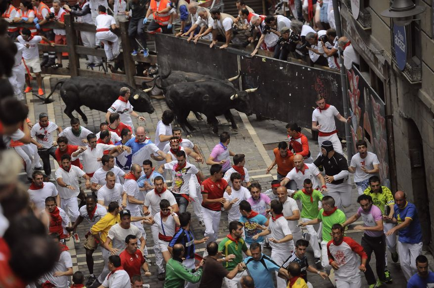 "A ""Fuente Ymbror"" fighting bull runs behind revelers during the running of the bulls at the San Fermin festival, in Pamplona, Spain, Saturday, July 13, 2013. Revelers from around the world arrive in Pamplona every year to take part in some of the eight days of the running of the bulls glorified by Ernest Hemingway's 1926 novel ""The Sun Also Rises.""(AP Photo/Alvaro Barrientos)"