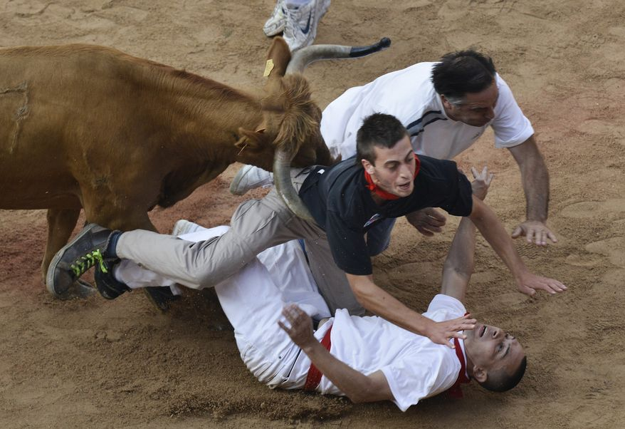 """Revelers are pushed over by a bull at the end of the last running of the bulls at the San Fermin festival, in Pamplona Spain on Sunday, July 14, 2013. Revelers from around the world arrive to Pamplona every year to take part in some of the eight days of the running of the bulls glorified by Ernest Hemingway's 1926 novel """"The Sun Also Rises."""" (AP Photo/Alvaro Barrientos)"""