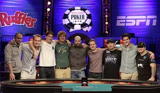 The nine remaining players who will make up the Final Table in November for the World Series of Poker pose for a photo, Tuesday, July 16, 2013, in Las Vegas. From left, they are, Sylvain Loosli, Michiel Brummelhuis, Mark Newhouse, Ryan Riess, Amir Lehavot, Marc McLaughlin, J.C. Tran, David Benefield and Jay Farber. (AP Photo/Julie Jacobson)