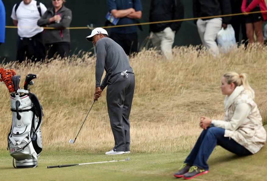 Tiger Woods plays a shot as his girlfriend US skier Lindsey Vonn, looks on during a practice round ahead of the British Open Golf Championship, Muirfield, Scotland, Monday, July 15, 2013. The British Open begins on Thursday, July 18. (AP Photo/Scott Heppell)