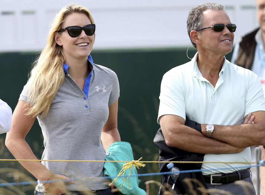 US skier Lindsey Vonn, left,  watches her boyfriend Tiger Woods, as he plays a practice round ahead of the British Open Golf Championship, Muirfield, Scotland Sunday, July 14, 2013. The British Open begins on Thursday July 18. (AP Photo/Scott Heppell)