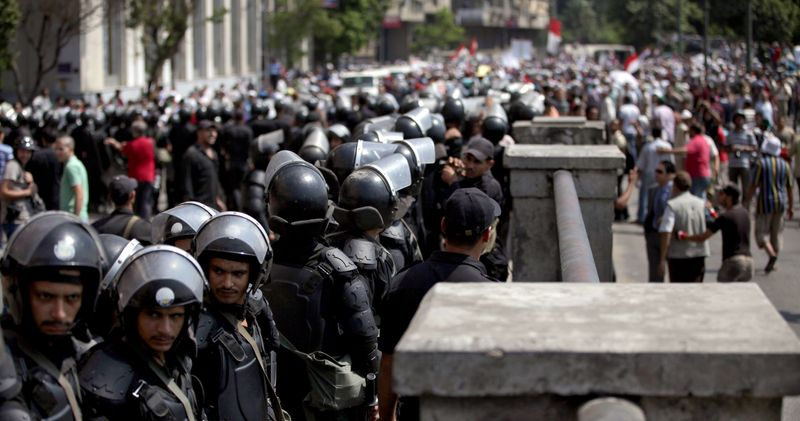 Egyptian riot police stand guard during a demonstration for supporters of ousted President Mohammed Morsi, near Tahrir Square in downtown Cairo, Egypt, Wednesday, July 17, 2013. Several hundred supporters of Egypt's deposed president massed outside the Cabinet building Wednesday in Cairo, expanding their protests denouncing the country's new government and demanding the reinstatement of Islamist leader Morsi. (AP Photo/Khalil Hamra)
