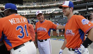 Manager Davey Johnson of the Washington Nationals, center, talks with Buster Posey of the San Francisco Giants, right, during batting practice for the MLB All-Star baseball game, on Monday, July 15, 2013 in New York. Hensley Meulens of the Giants is at left. (AP Photo/Kathy Willens)