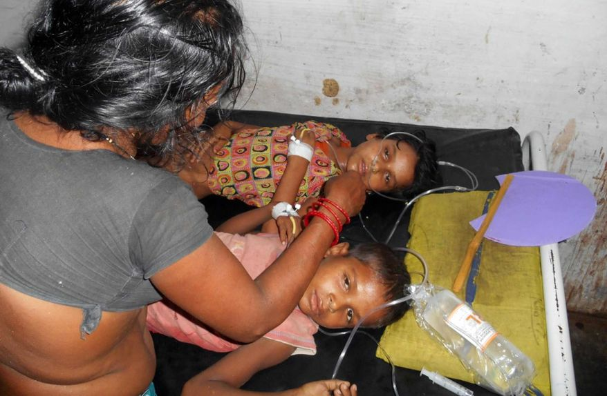 In this Tuesday, July 16, 2013, photo, schoolchildren receive treatment at a hospital after falling ill soon after eating a free meal at a primary school in Chhapra district, in the eastern Indian state of Bihar. (AP Photo)