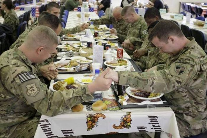 ** FILE ** U.S. soldiers pray before eating a Thanksgiving meal at a dining hall at the U.S.-led coalition base in Kabul, Afghanistan (Associated Press)