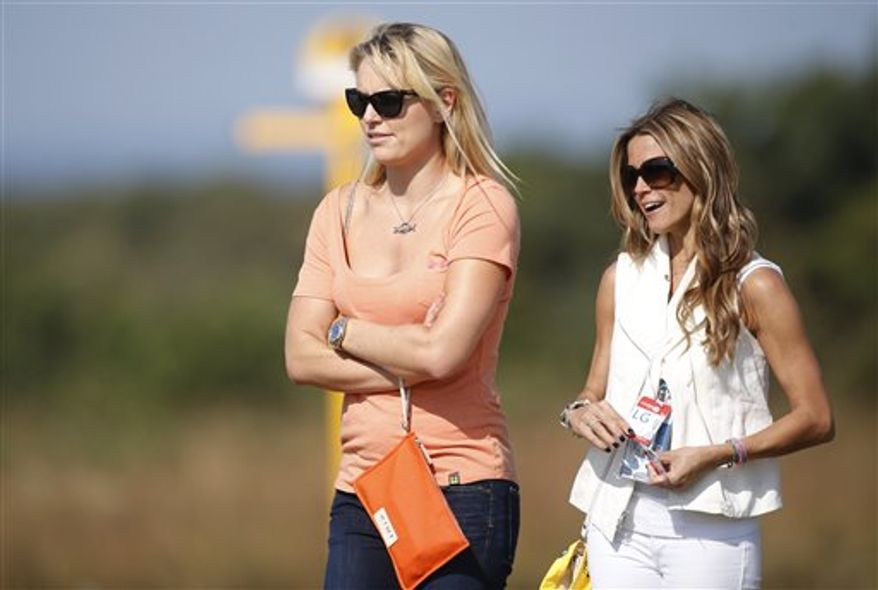 Lindsey Vonn, left, girlfriend of Tiger Woods of the United States, and Nadine Moze, girlfriend of Fred Couples of the United States watch a practice round ahead of the British Open Golf Championship at Muirfield, Scotland, Wednesday July 17, 2013. (AP Photo/Peter Morrison)