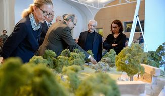 Architect Frank Gehry and others look over his design for the Eisenhower Memorial on the eastern end of the Mall at the National Building Museum on Thursday. (Andrew Harnik/The Washington Times)