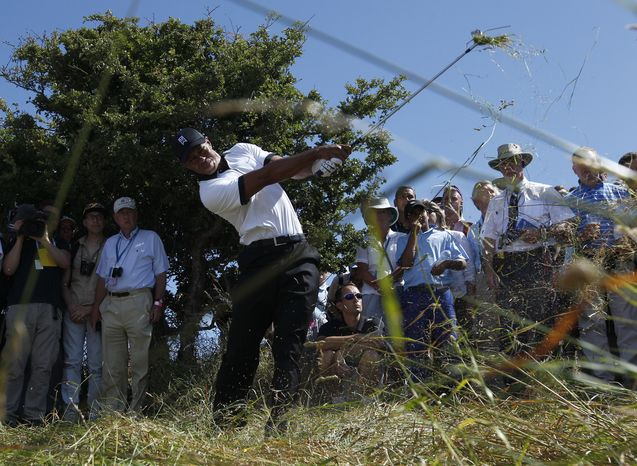 Tiger Woods of the United States plays out of the rough on the first fairway during the first round of the British Open Golf Championship at Muirfield, Scotland, Thursday, July 18, 2013. (AP Photo/Jon Super)
