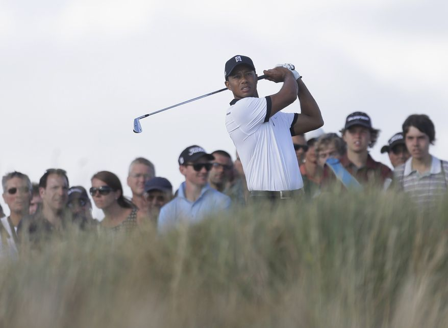 Tiger Woods of the United States plays a shot on the 13th hole during the first round of the British Open Golf Championship at Muirfield, Scotland, Thursday July 18, 2013. (AP Photo/Jon Super)