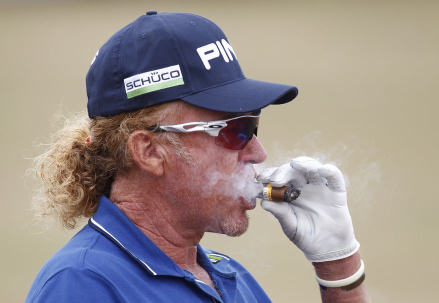 Miguel Angel Jimenez of Spain smokes a cigar on the driving range ahead of the British Open Golf Championship at Muirfield, Scotland, Wednesday July 17, 2013. (AP Photo/Jon Super)