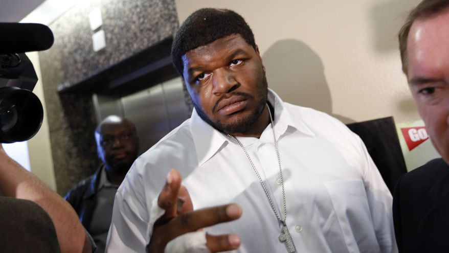 """FILE - In this Dec. 18, 2012 file photo, Dallas Cowboys defensive tackle Josh Brent, center, and his attorney George Miller, obscured at right, leave court in Dallas. Brent says he is retiring from football as he faces trial for a fatal crash that killed a teammate. Brent's agent, Peter Schaffer, said Thursday, July 18, 2013, that the 25-year-old Brent was """"taking care of his priorities."""" (AP Photo/David Woo, Pool, File)"""