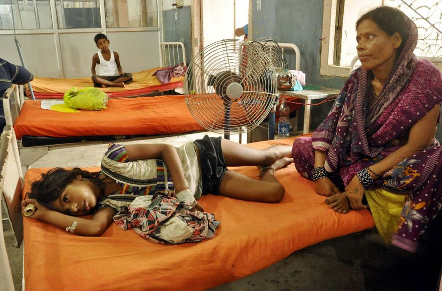 On Thursday, July 18, 2013, an Indian woman at a hospital in Patna, India, sits beside a child who fell sick after eating a free school lunch that was tainted with insecticide. Officials said 23 children died and more than two dozen others were sickened. (AP Photo/Aftab Alam Siddiqui)