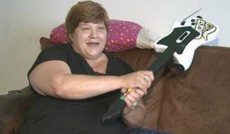 Melinda Walker fought off three would-be criminals with a 'Guitar Hero' set. (Image: News Channel 15, Indiana)