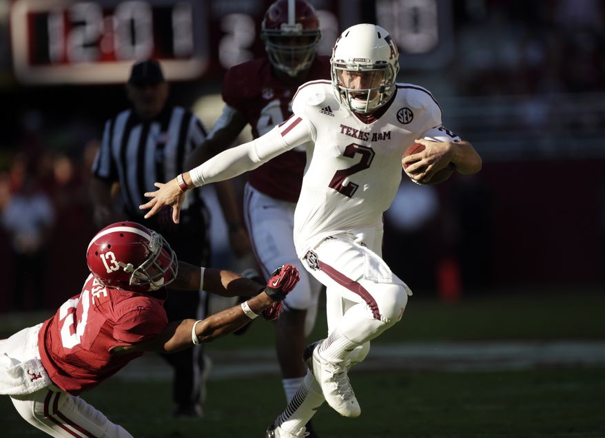 FILE - In this Nov. 10, 2012 file photo, Texas A&M quarterback Johnny Manziel (2) runs through the tackle of Alabama defensive back Deion Belue (13) during the first half of an NCAA college football game at Bryant-Denny Stadium in Tuscaloosa, Ala. (AP Photo/Dave Martin, File)