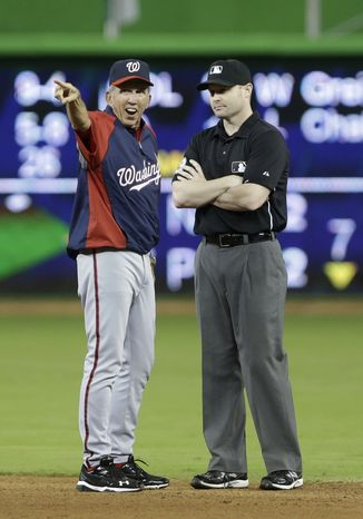 Washington Nationals manager Davey Johnson, left, argues a call with second base umpire Mike Estabrook after Miami Marlins second baseman Derek Dietrich tagged out Ian Desmond when Desmond attempted to steal second during the eighth inning of a baseball game, Saturday, July 13, 2013 in Miami. The Marlins defeated the Nationals 2-1 in 10 innings. (AP Photo/Wilfredo Lee)