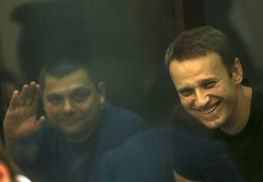 Russian opposition leader Alexei Navalny, right, and his former colleague Pyotr Ofitserov, left, are seen through a cage window in a courtroom in Kirov, Russia, on Friday, July 19, 2013. (AP Photo/Evgeny Feldman)