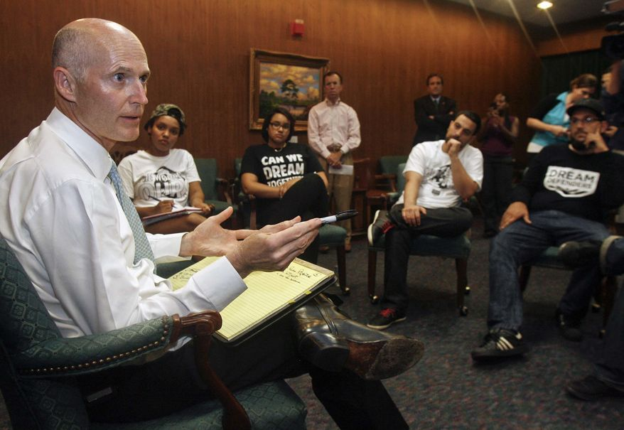 Florida Gov. Rick Scott speaks to protesters on Thursday, July 18, 2013, in the Capitol in Tallahassee, Fla. He told the demonstrators that he will not ask lawmakers to revamp the state's self-defense laws. (AP Photo/Phil Sears)
