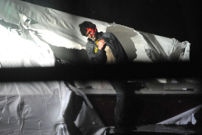 Dzhokhar Tsarnaev emerges from the boat, a laser from a sniper's rifle illuminating his forehead. (Sgt. Sean Murphy)