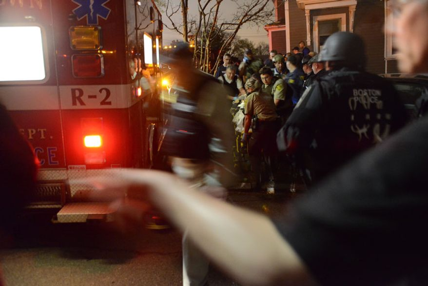 Dzhokhar Tsarnaev loaded into an ambulance after his capture. (credit: Sean Murphy)