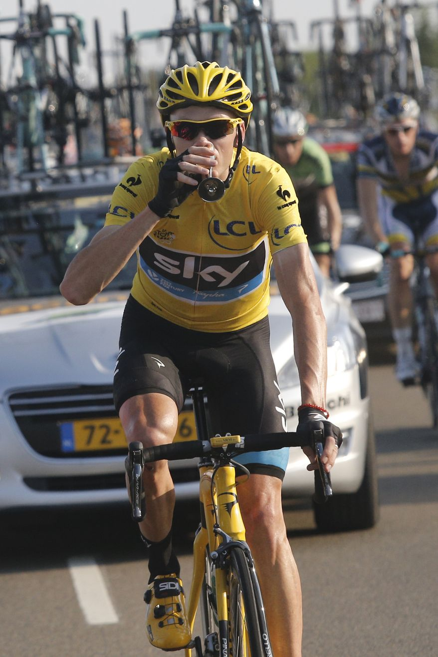 Christopher Froome of Britain, wearing the overall leader's yellow jersey, drinks a glass of champagne at his team car during the 21st and last stage of the 100th edition of the Tour de France cycling race over 133.5 kilometers (83.4 miles) with start in Versailles and finish in Paris, France, Sunday July 21 2013. (AP Photo/Laurent Cipriani)