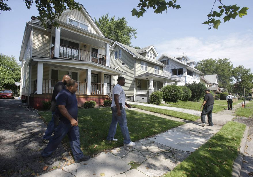 Police officers search a neighborhood in East Cleveland, Ohio, on Sunday, July 21, 2013, near where three bodies were found recently. The bodies, believed to be female, were discovered about 100 to 200 yards apart, and a 35-year-old man was arrested and is a suspect in all three deaths, though he has not yet been charged, East Cleveland Mayor Gary Norton said Saturday. (AP Photo/Tony
