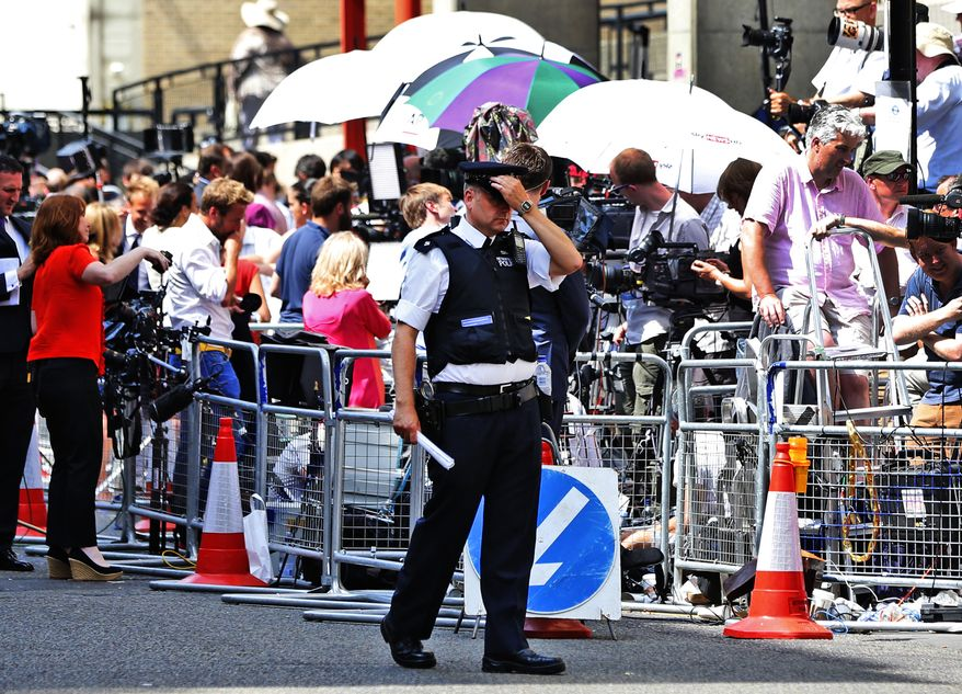 A British police, backdropped by members of the media, walks outside St. Mary's Hospital exclusive Lindo Wing in London, Monday, July 22, 2013. Buckingham Palace officials say Prince William's wife, Kate, has been admitted to the hospital in the early stages of labour. Royal officials said that Kate traveled by car to St. Mary's Hospital in central London. Kate _ also known as the Duchess of Cambridge _ is expected to give birth in the private Lindo Wing of the hospital, where Princess Diana gave birth to William and his younger brother, Prince Harry.The baby will be third in line for the British throne _ behind Prince Charles and William _ and is anticipated eventually to become king or queen.(AP Photo/Lefteris Pitarakis)