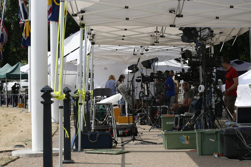 Broadcast media prepare to report from outside Buckingham Palace in London where a notice announcing the birth of the baby will be posted, Monday, July 22, 2013. Buckingham Palace officials say Prince William's wife, Kate, Duchess of Cambridge, has been admitted to St Mary's Hospital in the early stages of labour. (AP Photo/Sang Tan)
