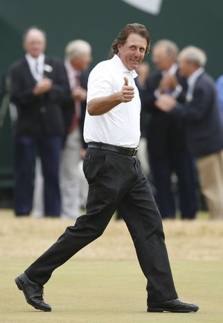 Phil Mickelson of the United States gestures on his way to receiving the Claret Jug trophy after winning the British Open Golf Championship at Muirfield, Scotland, Sunday July 21, 2013. (AP Photo/Matt Dunham)