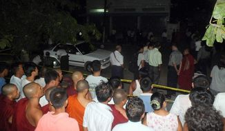 In this photo taken Sunday, July 21, 2013, Buddhist monks and residents watch police examining a car after an explosion in Mandalay, central Myanmar. A small explosion went off Sunday near a firebrand monk as he was giving a sermon during a Buddhist ceremony, wounding five people, police and witnesses said Monday. (AP Photo)
