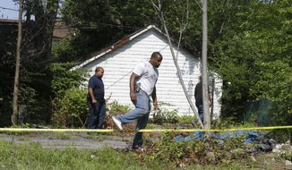 East Cleveland police search Sunday, July 21, 2013, near where three bodies were recently found, in East Cleveland, Ohio. The bodies, believed to be female, were found about 100 to 200 yards (90 to 180 meters) apart, and a 35-year-old man was arrested and is a suspect in all three deaths, though he has not yet been charged, East Cleveland Mayor Gary Norton said Saturday. (AP Photo/Tony Dejak)