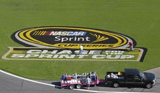 **FILE** Workers paint a logo on the grass near the front stretch during preparation for Saturday's NASCAR Sprint Cup Series auto race in Concord, N.C., Wednesday, Oct. 10, 2012. (AP Photo/Chuck Burton)