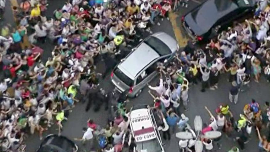 In this image from video, a crowd mobs the silver Fiat carrying Pope Francis through Rio de Janeiro on Monday, July 22, 2013. Ecstatic believers forced the closed Fiat to stop several times as they swarmed around during the drive from the airport to an official opening ceremony in the center of the city. (AP Photo)