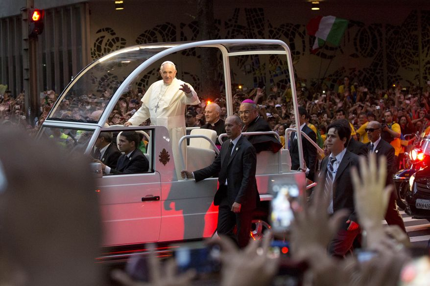 Pope Francis waves from his popemobile as he made his way into central Rio de Janeiro, Brazil, Monday, July 22, 2013. The pontiff arrived for a seven-day visit in Brazil, the world's most populous Roman Catholic nation. During his visit, Francis will meet with legions of young Roman Catholics converging on Rio for the church's World Youth Day festival.(AP Photo/Felipe Dana)